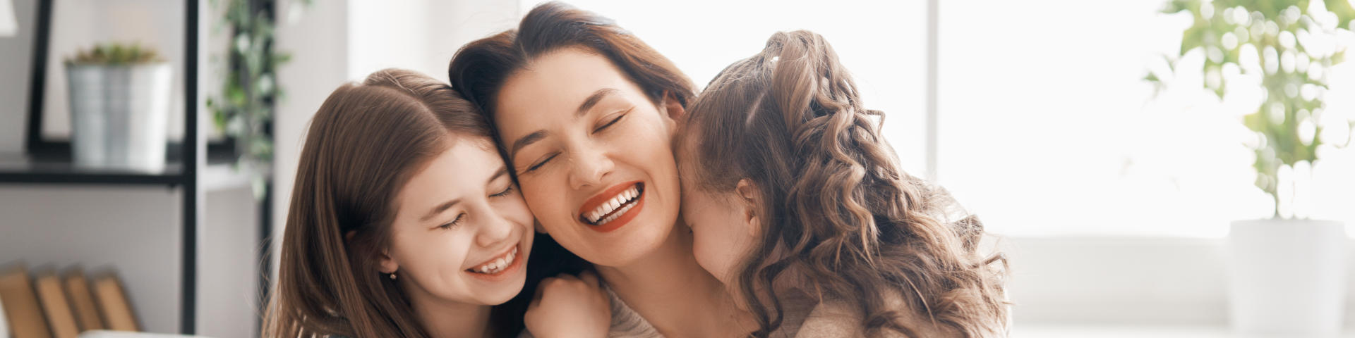 happy mother hugging her two cheerful little girls